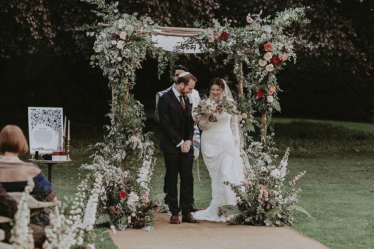 Bride and Groom Underneath Floral Chuppa