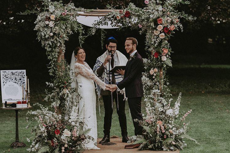 Bride and Groom Making Wedding Vows Underneath Floral Chuppa