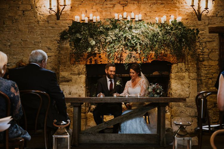 Grand Fireplace with Greenery Garland | Bride in Annasul Y Violet Bridal Gown | Groom in Suit Supply | Rustic Cripps Barn Winter Wedding | Alexandra Jane Photography