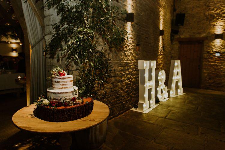 Semi Naked Wedding Cake on Tree Slice Cake Stand | Giant Light Up Letters | Rustic Cripps Barn Winter Wedding | Alexandra Jane Photography