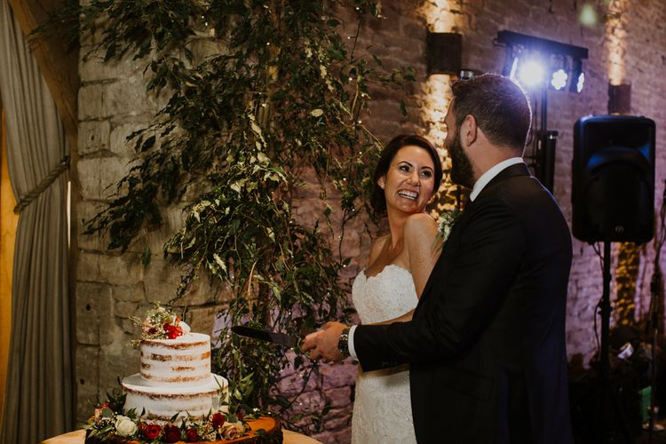 Cutting the Cake | Bride in Annasul Y Violet Bridal Gown | Groom in Suit Supply | Rustic Cripps Barn Winter Wedding | Alexandra Jane Photography