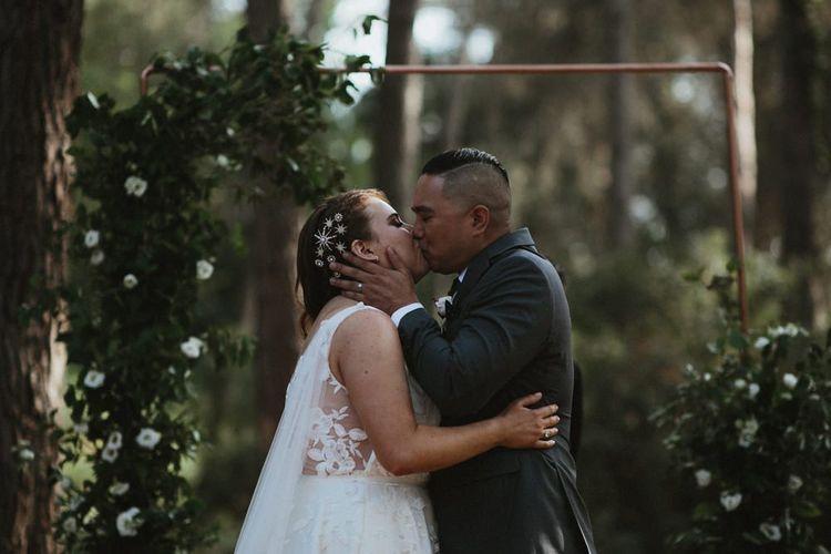 Bride and groom kiss as newlyweds