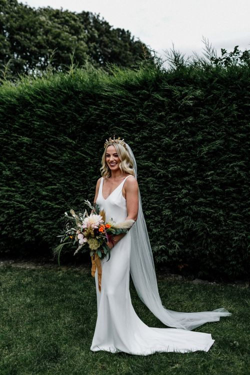 Stylish bride in slip wedding dress and gold bridal crown holding  an oversized bouquet