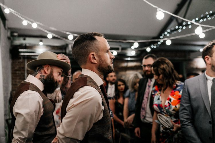 Groom standing at the altar in brown check waistcoat