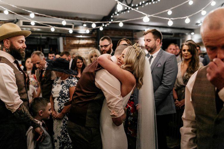 Bride and groom hugging under festoon lights.