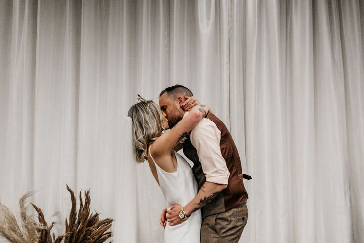 Bride and groom embracing during wedding ceremony at New Craven Hall
