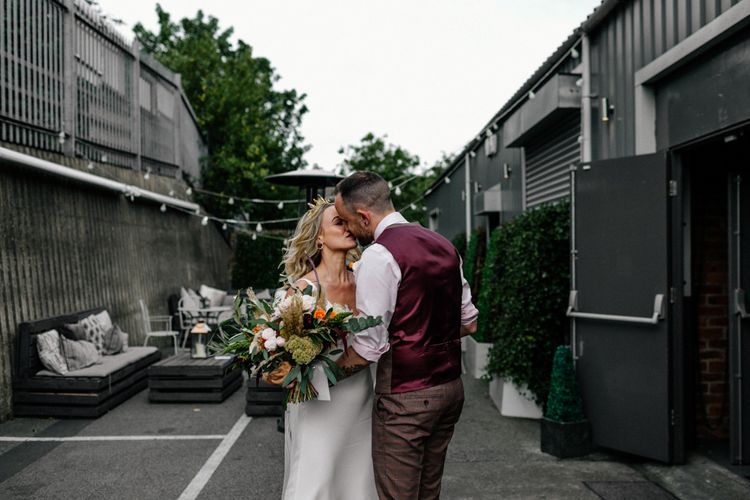 Bride and groom kissing in the courtyard at New Craven Hall , Leeds