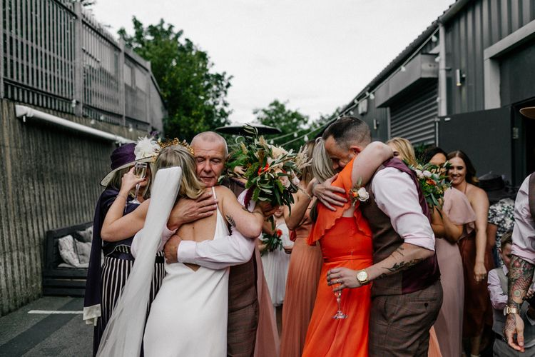 Wedding guests hugging the bride and groom