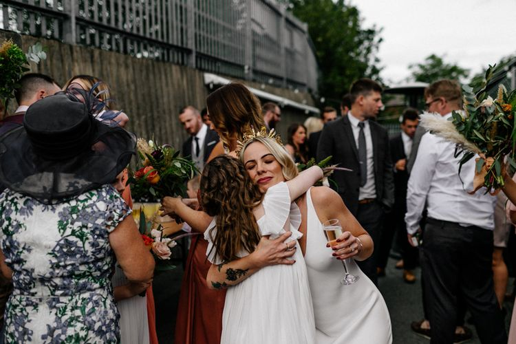 Stylish bride in gold crown hugging the flower girl