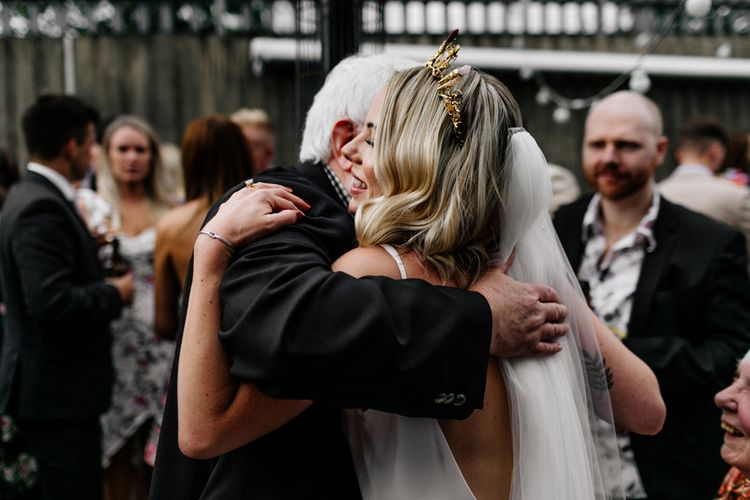 Wedding guest hugging the bride in gold crown