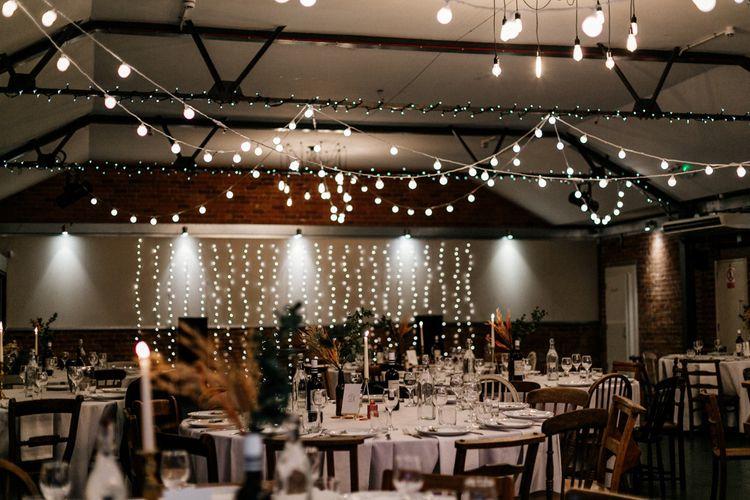 Festoon and fairy light decor at industrial wedding venue