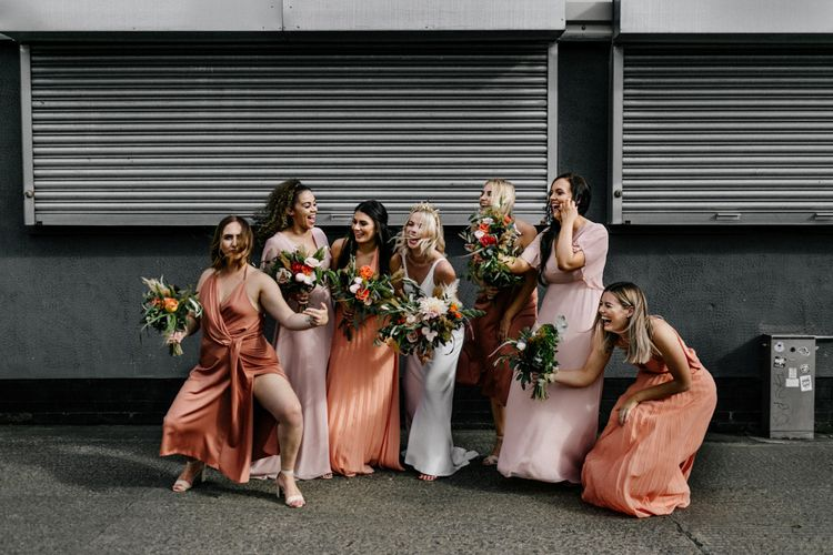 Fun bridal party portrait with bridesmaids in coral dresses