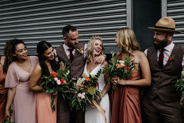 Bride in gold crown laughing with her bridesmaid
