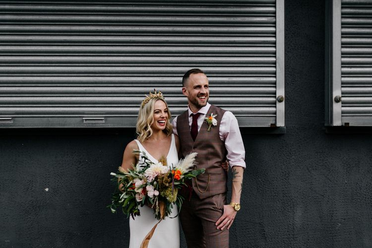 Stylish bride and groom portrait in front of metal shutters