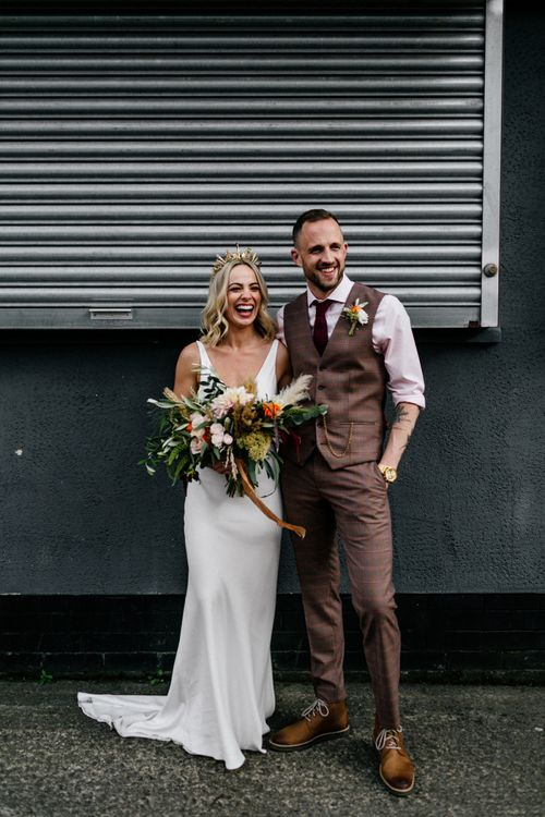 Bride in minimalist wedding dress and gold bridal crown and groom in brown check waistcoat