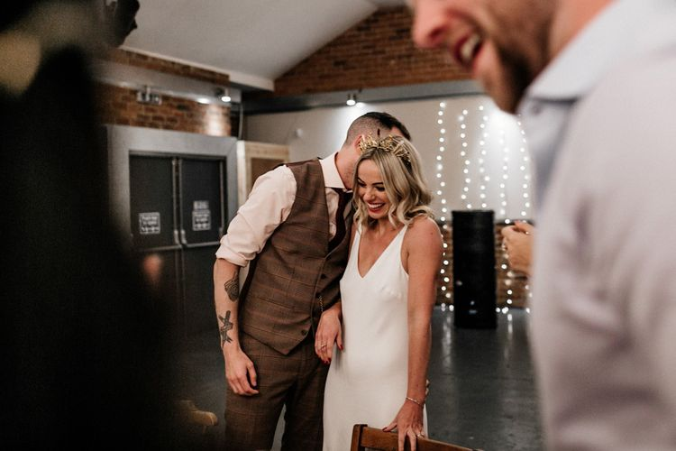Groom whispering something in his brides ear