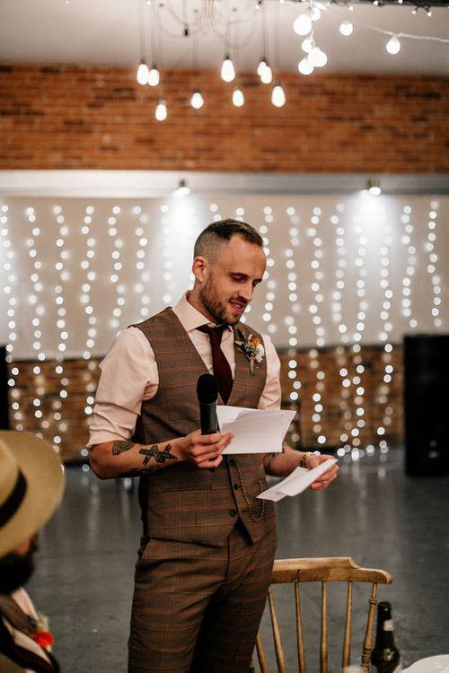 Groom in brown check waistcoat delivering his wedding speech