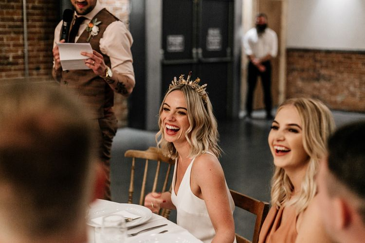 bride in gold crown smiling at wedding speeches