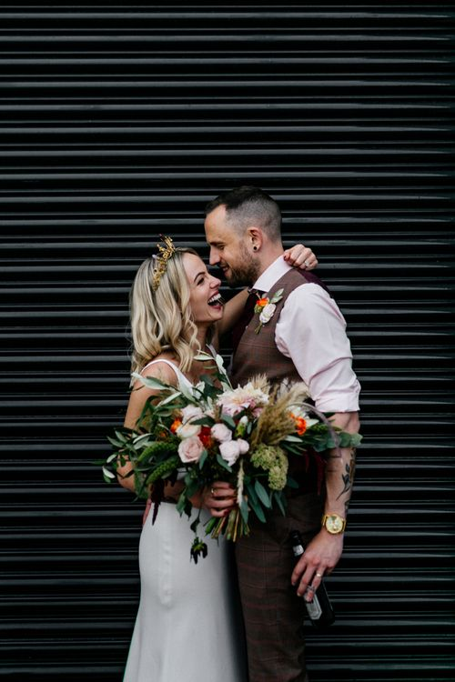 Bride in gold crown holding an oversized bouquet