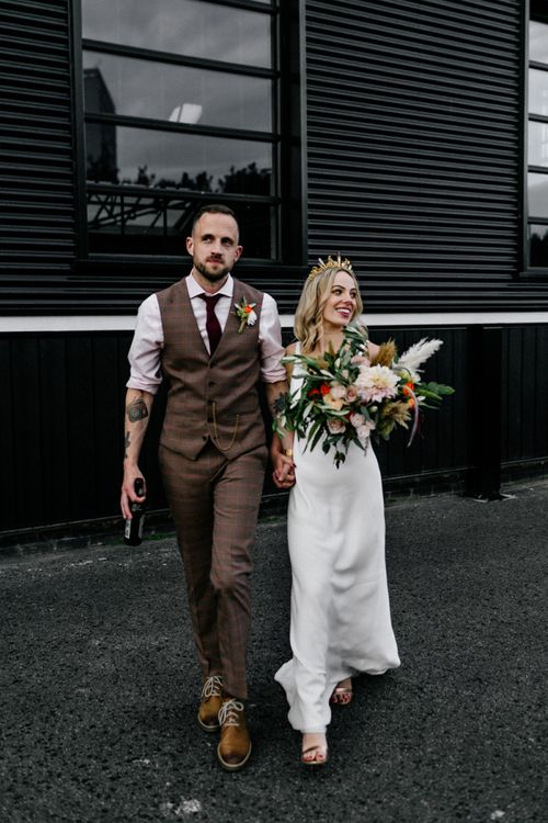 Stylish bride in minimalist wedding dress and groom in check trousers and waistcoat
