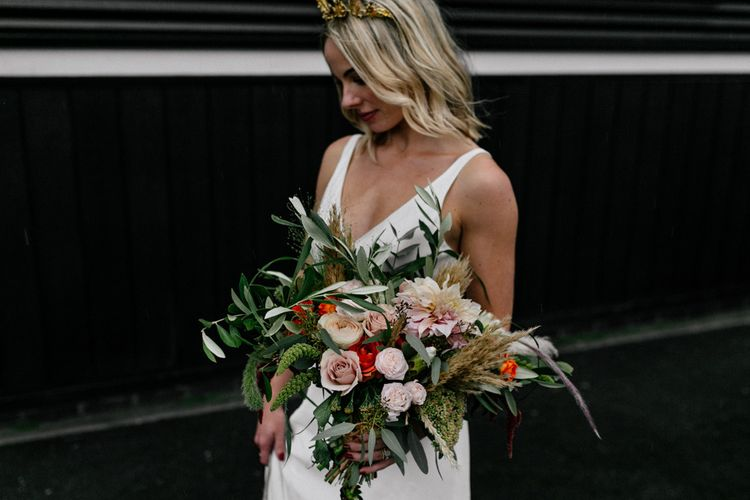 Stylish bride holding an oversized bouquet with  blush pink flowers and foliage