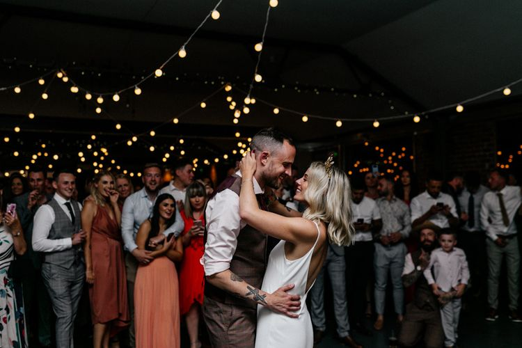 Bride and groom first dance with festoon light canopy