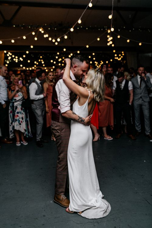 Stylish bride and groom in slip wedding dress, gold bridal crown and waistcoat taking their first dance
