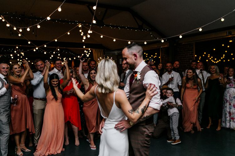 Bride and groom waving at wedding guests on the dance floor