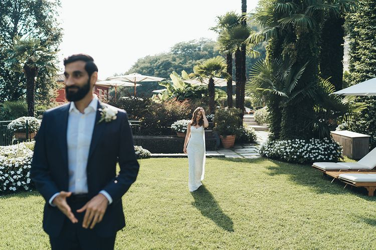 Bride in Grace Loves Lace Wedding Dress Approaching Groo in Navy Suit for First Look