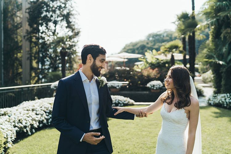 Bride in Grace Loves Lace Wedding Dress Approaching Groom in Navy Suit for First Look