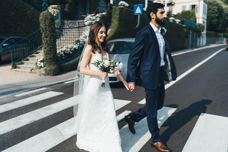 Bride in Grace Loves Lace Mia Wedding Dress and Groom in Taliare Navy Suit Walking Across a Zebra Crossing