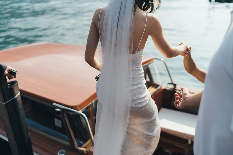 Bride in Grace loves Lace Mia Wedding Dress and Cathedral Length Veil Getting onto Boat on Lake Como