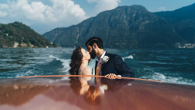 Bride in Grace Loves Lace Mia Wedding Dress and Groom in Taliare Navy Suit Kissing on Boat Ride Over Lake Como