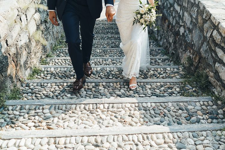 Groom in Navy Suit with Monk Strap Shoes and Bride in Lace Wedding Dress with Strappy Sandals
