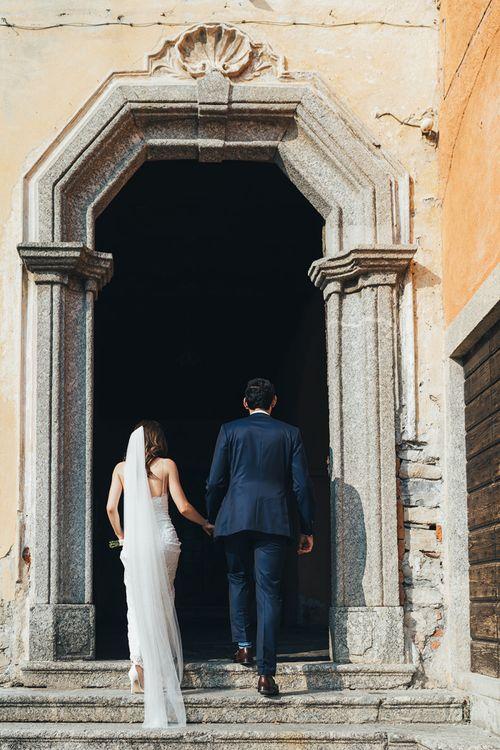 Bride in Grace Loves Lace Mia Wedding Dress and Groom in Taliare Navy Suit Entering Wedding Ceremony Venue