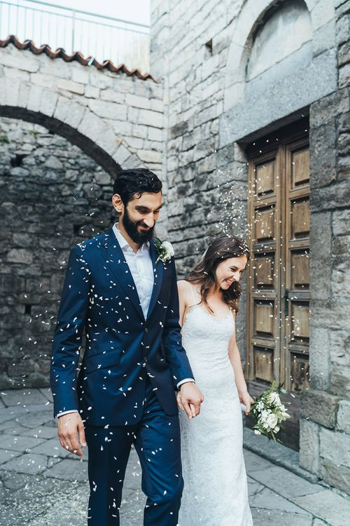 Confetti Exit with Bride in Grace Loves Lace Mia Wedding Dress and Groom in Taliare Navy Suit