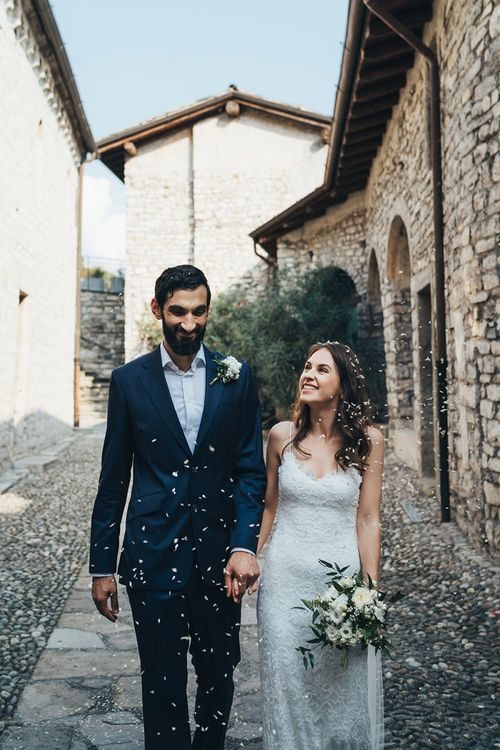Just Married Confetti Moment with Bride in Grace Loves Lace Mia Wedding Dress and Groom in Taliare Navy Suit