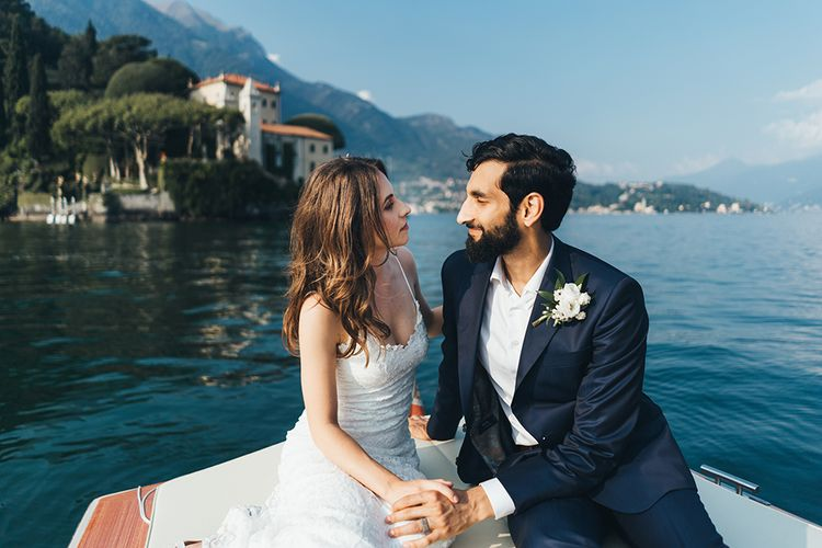 Bride in Grace Loves Lace Mia Wedding Dress and Groom in Taliare Navy Suit Enjoying a Boat Ride Over Lake Como