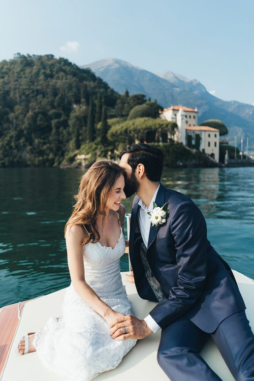 Laughing Bride in Grace Loves Lace Mia Wedding Dress and Groom in Taliare Navy Suit Enjoying a Boat Ride Over Lake Como