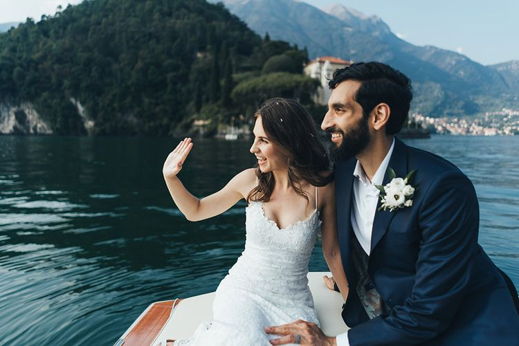 Waving Bride in Grace Loves Lace Mia Wedding Dress and Groom in Taliare Navy Suit Enjoying a Boat Ride Over Lake Como