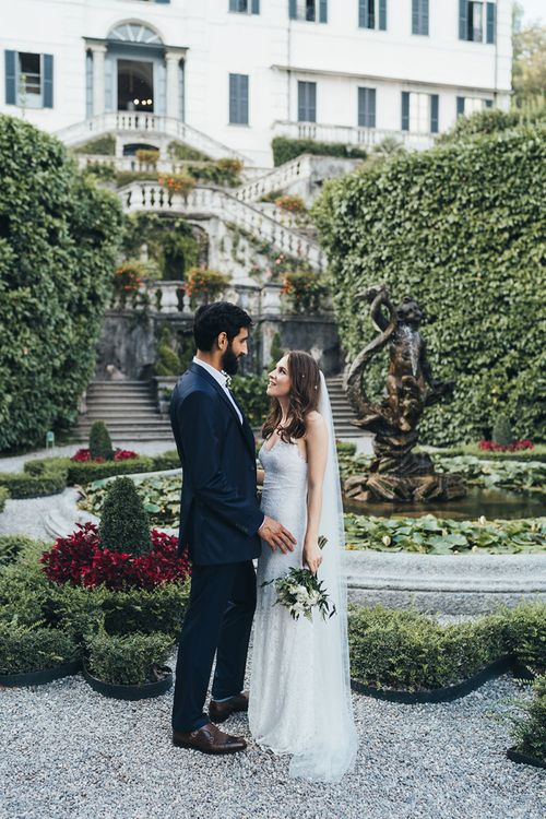 Portrait of Bride in Grace Loves Lace Mia Wedding Dress and Groom in Taliare Navy Suit
