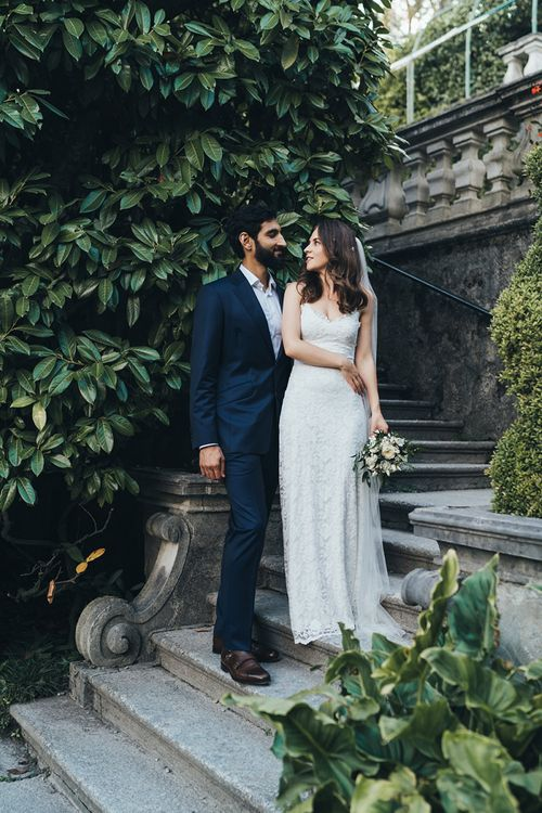 Bride in Grace Loves Lace Mia Wedding Dress and Groom in Taliare Navy Suit Embracing on Steps