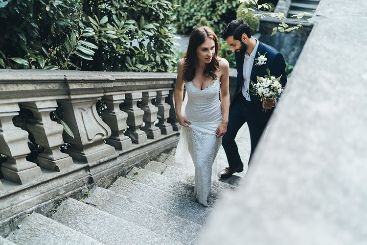 Bride in Grace Loves Lace Mia Wedding Dress and Groom in Taliare Navy Suit Walking up Steps