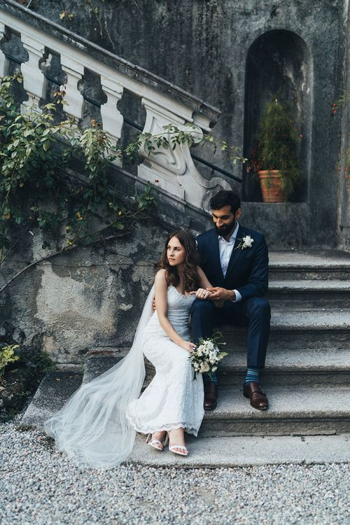 Bride in Grace Loves Lace Mia Wedding Dress and Groom in Taliare Navy Suit Sitting on Steps