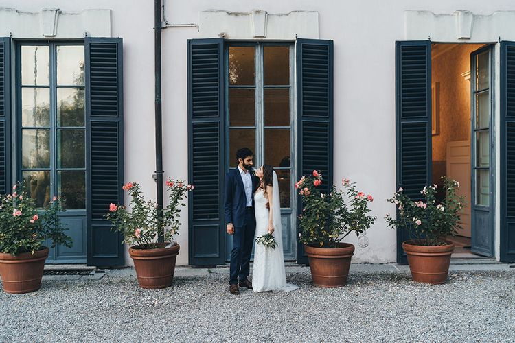 Bride in Grace Loves Lace Mia Wedding Dress and Groom in Taliare Navy Suit Standing in Front of giant Window Shutters