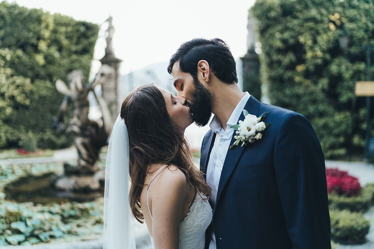 Bride in Grace Loves Lace Mia Wedding Dress and Groom in Taliare Navy Suit  Kissing in Garden