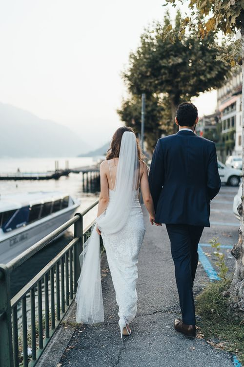 Bride in Grace Loves Lace Mia Wedding Dress and Groom in Taliare Navy Suit Walking Around Lake Como