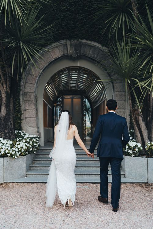 Bride in Grace Loves Lace Mia Wedding Dress and Groom in Taliare Navy Suit Going to Intimate Wedding Reception