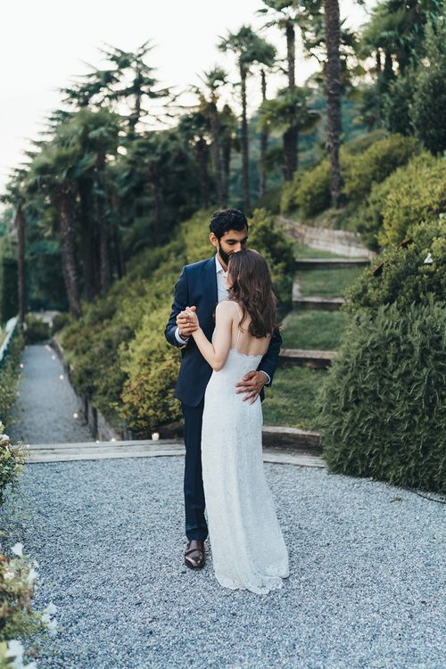 Bride in Grace Loves Lace Mia Wedding Dress and Groom in Taliare Navy Suit Embracing in Gardens