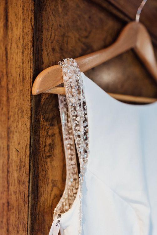 Close up detail of brides embellished gown at same sex woodland wedding celebration  in autumn